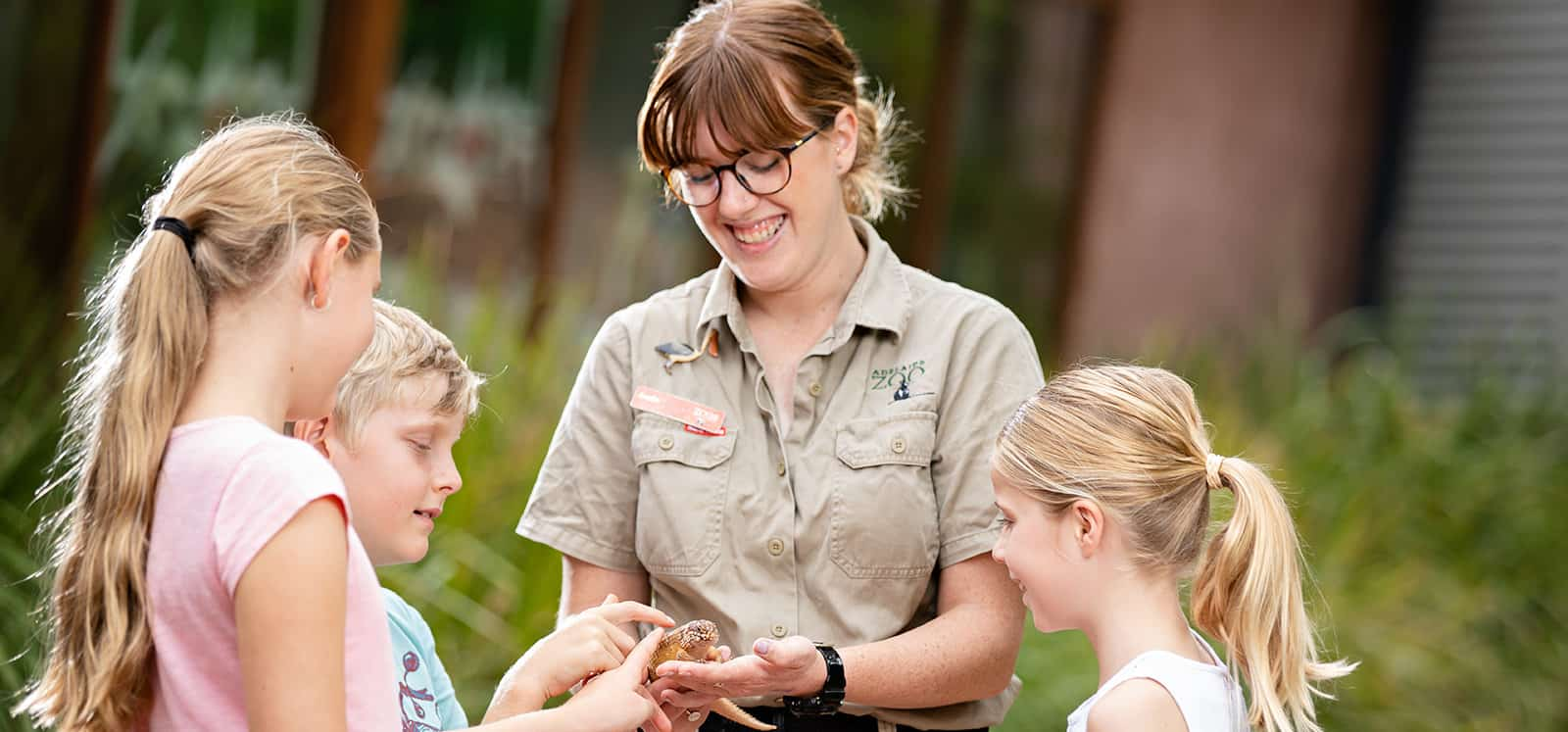 Kids smiling as Adelaide Zoo keeper holds lizard